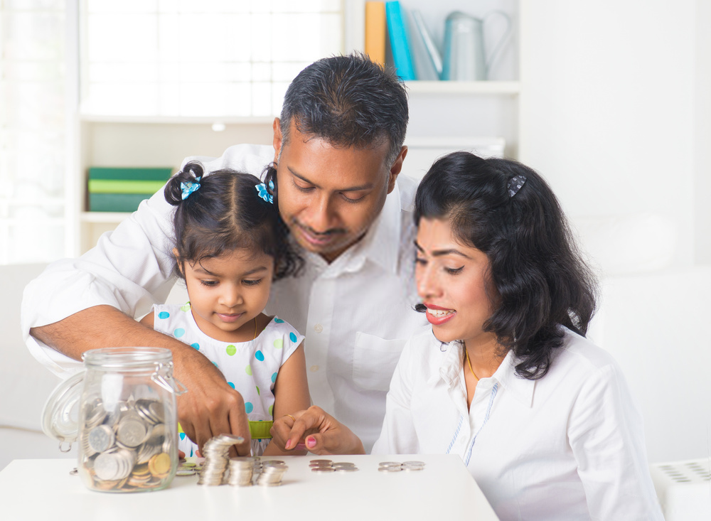 Malaysian Parents teaching child how to save money and plan financially for the future