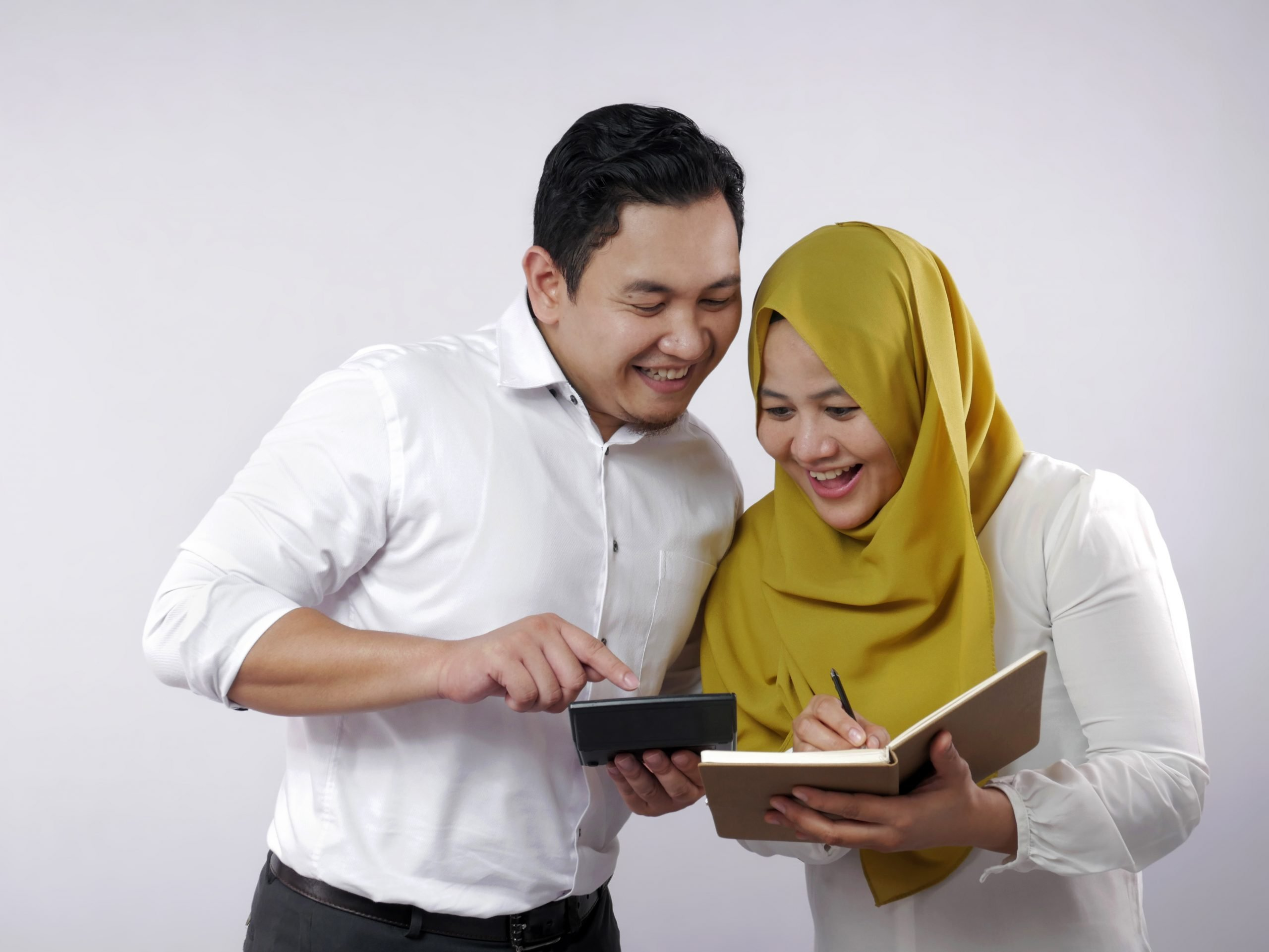 Muslim Couple Analyzing Financial Management Report